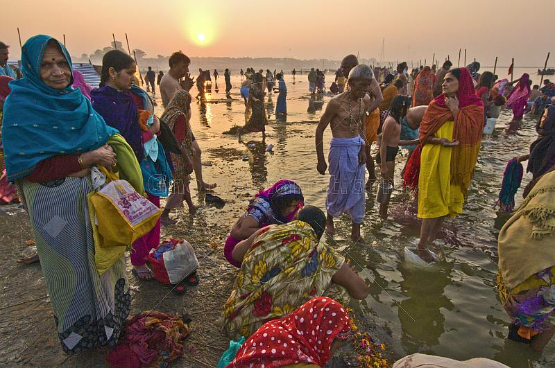 Male and female pilgrims prepare for ritual bathing in Ganges river at dawn.