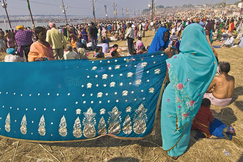 Woman dries blue Sari whilst watching bathing crowds in warm sunshine at Ganges Sangam.