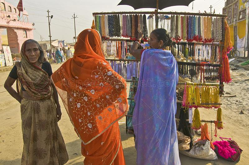 Three women in saris look at necklace jewellery stall at Kumbh Mela festival.