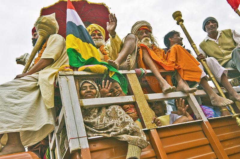 Hindu pilgrims wave from a truck in Basant Panchami Snana procession.