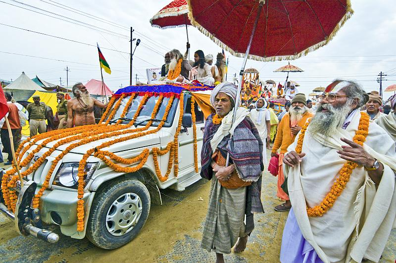 Holy Man with ceremonial umbrella walks in Basant Panchami Snana procession.