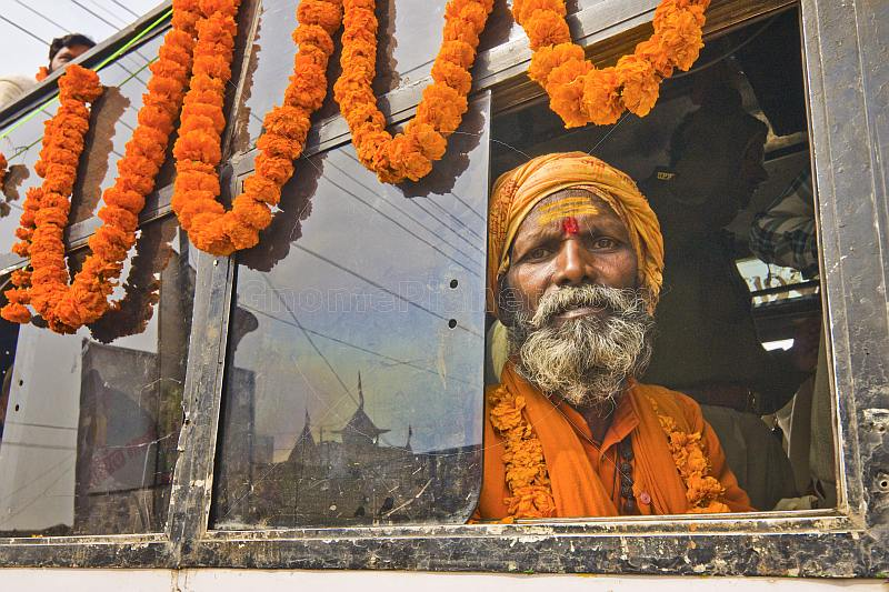 Elderly saffron-clad Hindu Holy Man looks from decorated bus window.