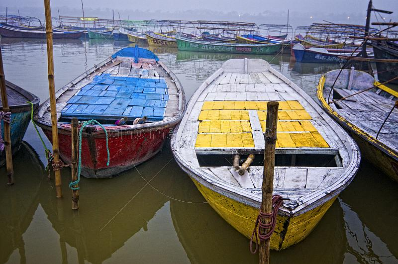 Deserted blue and yellow rowing boats wait for hire by Sangam Hindu pilgrims.