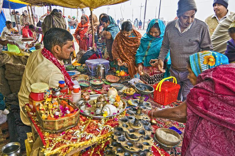 Hindu Holy Man provides religious requirements for Pilgrims at Kumbh Mela festival.
