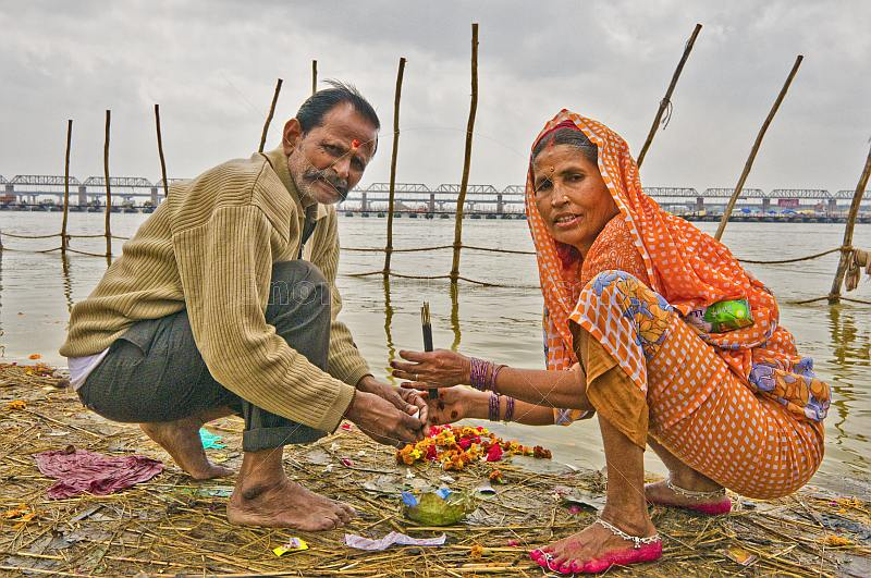 Hindu pilgrim married couple perform private ceremony next to Ganges river Sangam.