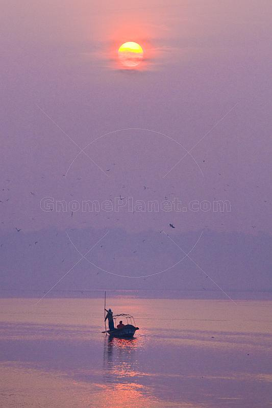 Solitary rowing boat with pilgrim visits Sangam on River Ganges in early dawn light.