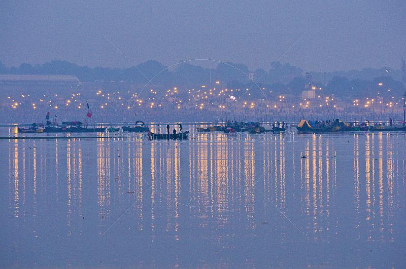 Rowing boats take pilgrims to visit Ganges Yamuna river Sangam before dawn.