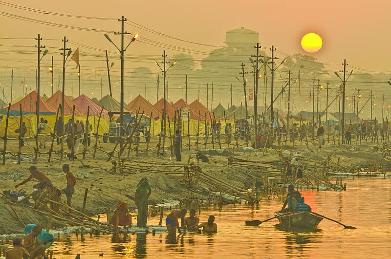 Rowing boat passes bathing pilgrims and tents next to River Ganges in early dawn light.