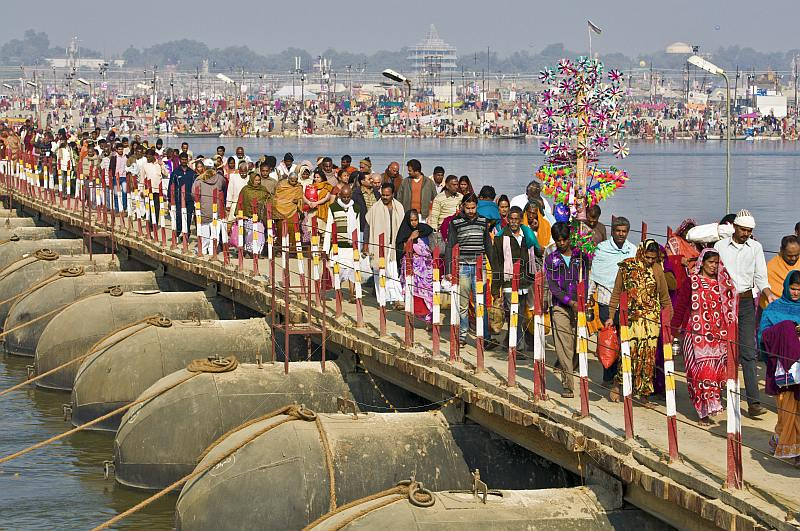 Long lines of Indian Hindu pilgrims cross pontoon bridge over Ganges river.