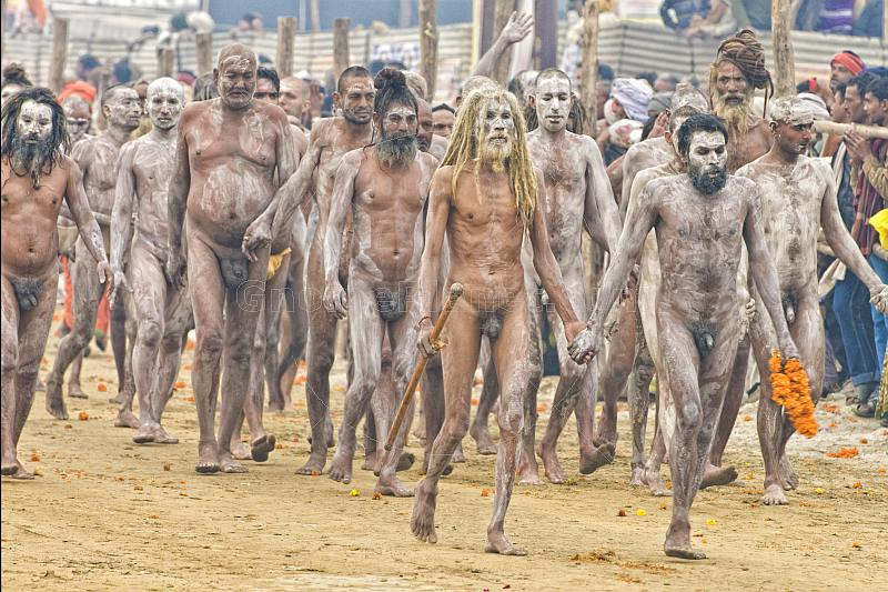 Ash-smeared Naga Holy Men walk in procession from Ganges river bathing ceremony.