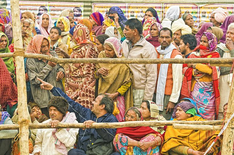 Villager pilgrims crowd behind barriers to see Basant Panchami Snana procession.