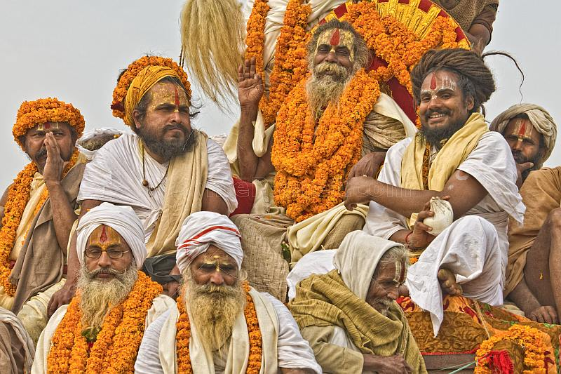 Group of Hindu Holy Men decorated with marigolds on processional truck roof.