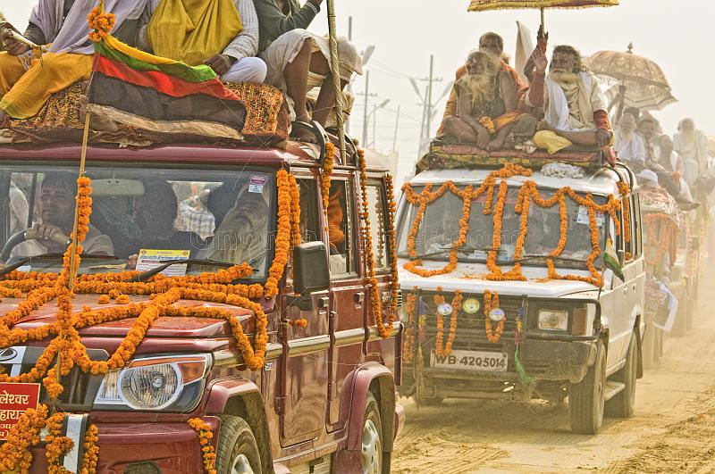 Decorated trucks drive through dust clouds in Basant Panchami Snana procession.