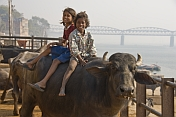Indian girl and boy riding a buffalo, on the banks of the Ganga River.