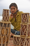 A young Indian man selling drums.