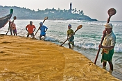 Fishermen use their oars to stop the fishing net getting washed back out to sea.