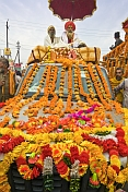 Two Holy Men On Roof Of Flower Decorated Jeep