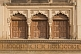 Three ancient brown wooden doors set in carved sandstone frames.
