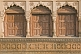 Image of Three ancient brown wooden doors set in carved sandstone frames.
