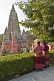 Two Tibetan lady pilgrims rest from their devotions to look at the Mahabodhi Temple.