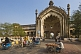 Cycle rickshaws drive through the elaborate gateway of the Rumi Darwaza.