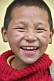 Smiling Buddhist monk in red jersey.
