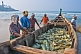 Fishermen with day's catch stored in boat on beach.