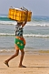 Image of Man on the beach carrying a box of fish on his head.