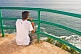 A young Indian male tourist looks out to sea from the observation gallery of Vizhinjam Lighthouse.