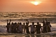 Indian boys dance in the waves at sunset.