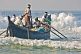 Image of Fishermen battle the waves to launch their boat at Kovalam Beach.
