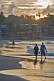 Image of Couple walk along Lighthouse Beach at dawn.