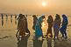 Women pilgrims in saris walk through muddy shallows to get to Ganges river bathing area.