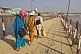 Barefoot village pilgrims carry belongings on head to cross Ganges River pontoon bridge.