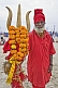 Hindu holy man dressed in red with marigold decorated brass trident for Lord Shiva.