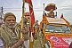 Hindu man holds flag for decorated Sadhu Truck in Kumbh Mela  parade.