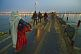 Pilgrims cross Ganges river pontoon bridge in pre-dawn light to join Kumbh Mela festival.