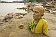 Statue Of Unknown Swami With Bald Head And Yellow Robes Buried In Ganges Mud