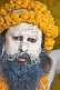 Juna Akhara Naga with Vibhuti sacred ash covered face and marigold flower garlands.