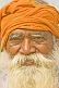 Smiling elderly Hindu Holy Man with orange turban and flowing white beard at Kumbh Mela.