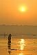 Woman in sari walks through Ganges River shallows at dawn for a ritual bath.