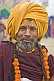 Smiling Hindu Holy Man with saffron-colored turban and marigold flower garlands.