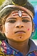 Boy with Hindu God face paint raises money from Kumbh Mela pilgrim visitors.