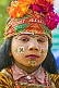Girl with face paint and flower filled turban raises money from Kumbh Mela pilgrim visitors.