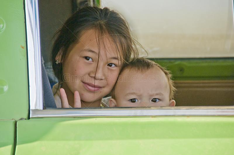 Kazakh girl and baby in a van at a village petrol filling station.