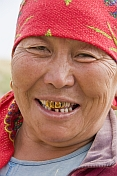 caption: Kazakh woman with red headscarf and gold teeth.
