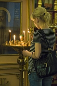 Worshipper lighting candles in front of icon at Saint Nicholas Cathedral.