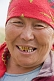 Kazakh woman with red headscarf and gold teeth.