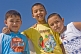 Three Kazakh boys pose for a photo in bright sunshine near the Aral sea.