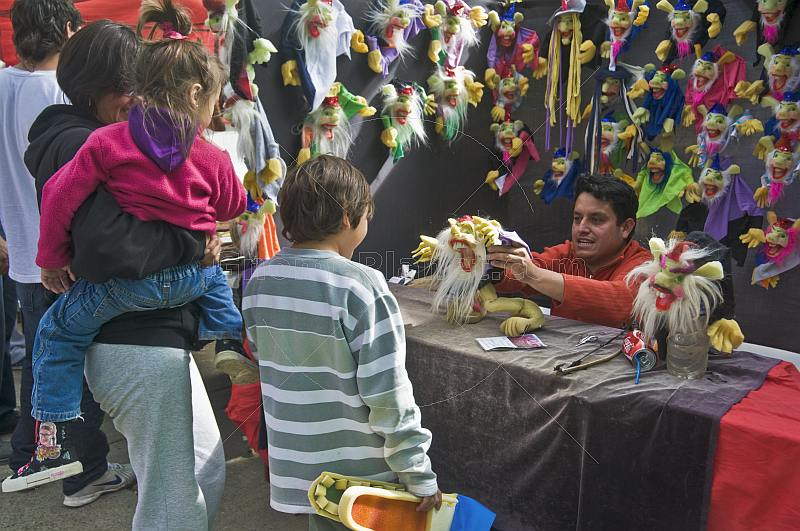 A puppet-maker shows his wares to visiting children.